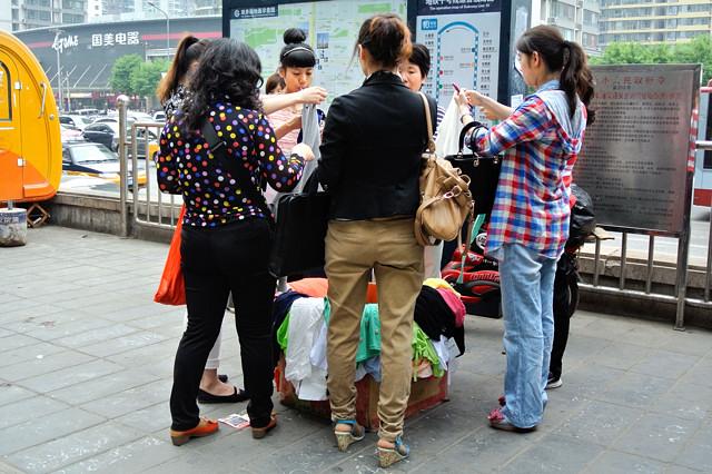 Tシャツの行商人に群がる中国人女子@北京双井駅